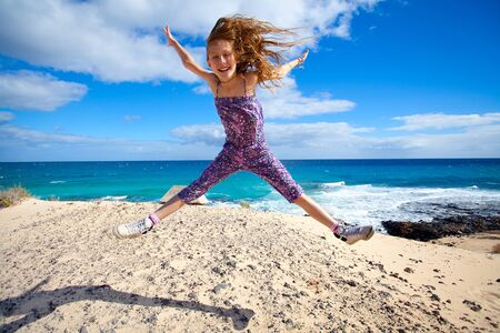 Happy girl full of excitement jumping on a beach Stock Photo