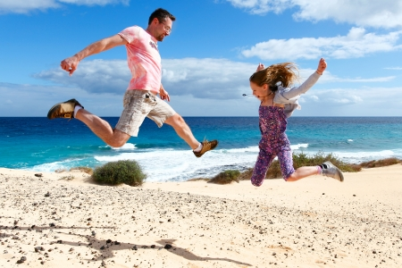 Happy people jumping on a beach. Vacations by the sea Stock Photo