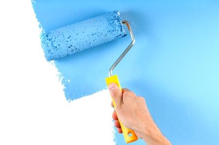 empleadas domesticas: Pared de la pintura de color azul con el rodillo Foto de archivo
