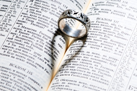 holy bible with silver ring and heart shape shadow photo