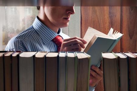 men reading a book next to the bookshelf