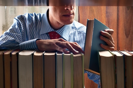 men put a book on to the bookshelf