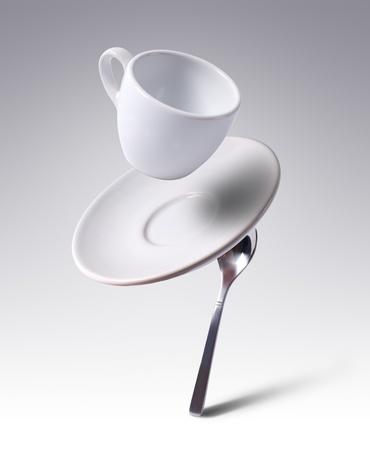 fallende Kaffeetasse mit Untertasse und Löffel Lizenzfreie Bilder