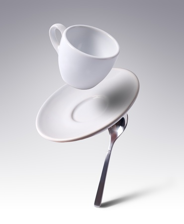 falling coffee cup with spoon and saucer photo