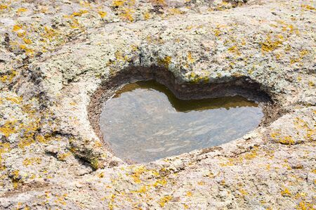 heart of stone: stone granite heart with puddle and moss