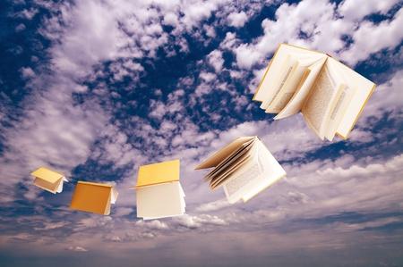 青い空を背景に飛んで書籍の群れ