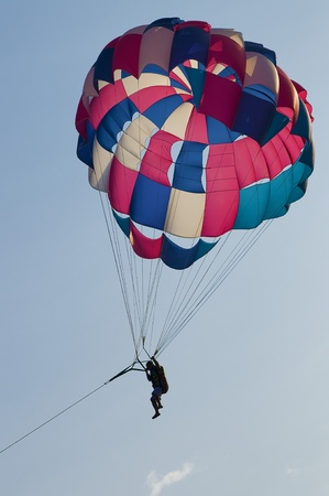 man flies to parachute in the sky