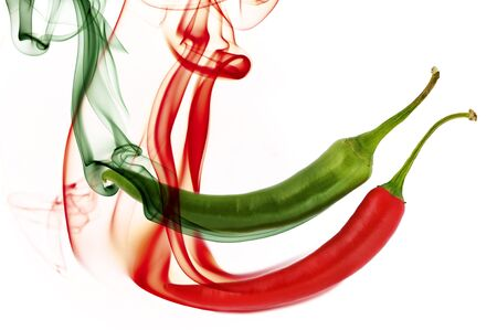 red and green hot chili pepper with color smoke on white Standard-Bild