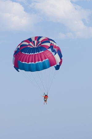 man flies to parachute in the sky photo