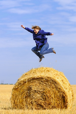 girl jumping up on straw roll photo