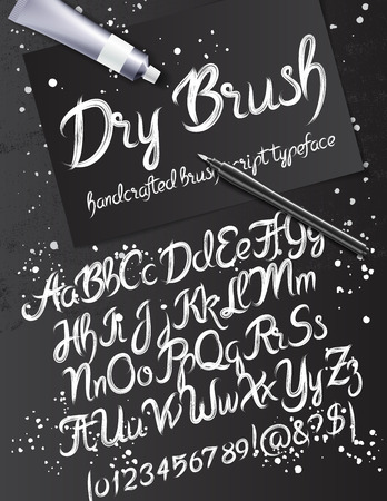 rollerbrush: Calligraphy mockup with dry brush typeface, pen and paint tube on the background of black sheet of paper and grunge table