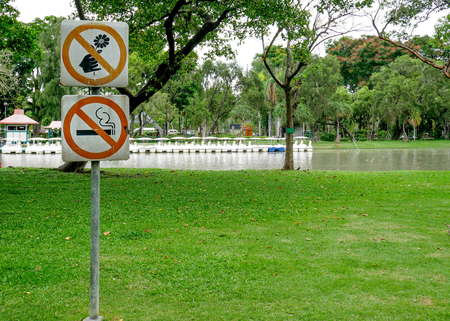 habit: The signs Do not pick flower metal sign, orange cycle color and Label no smoking metal sign, red cycle color in the park.