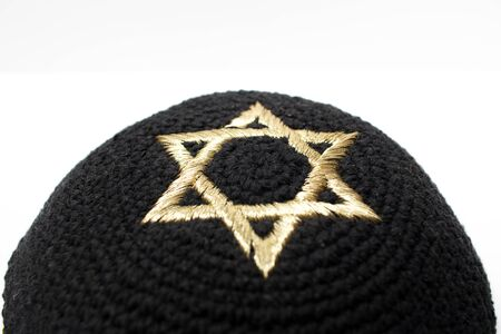 Closeup of a black kippah with a golden david star on top on a white background.