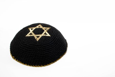 Israeli black Kippah with the david star on the top with a white background.