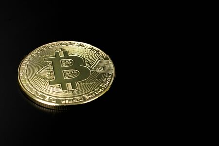 Closeup of a golden bitcoin coin with a dark black background. crypto currency. Imagens