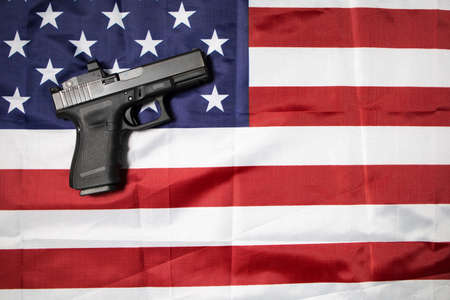 A handgun pistol on the American flag. Gun laws in the USA and self defense.