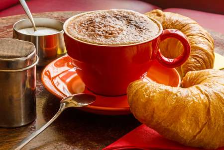 closeup of coffee with frothed milk, cocoa and croissants photo