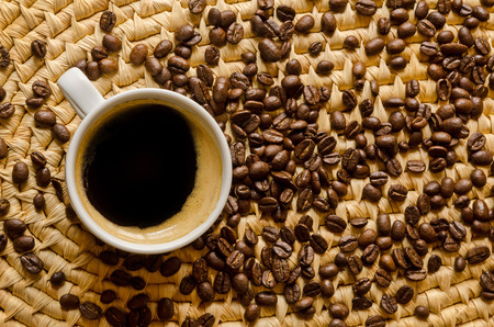 cup with coffee and espresso beans on a woven tray photo