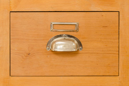 a single old cabinet drawer with metal handle photo