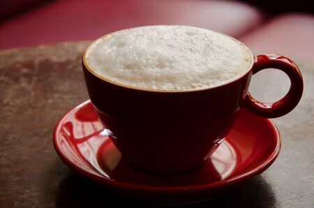 atmospheric: coffee mug with frothed milk in an atmospheric cafe Stock Photo