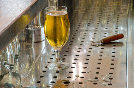 single beer: single beer glass and bottle opener behind the bar counter