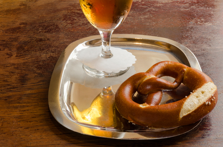 Pretzel and beer glass on a metal tray with a white serviette photo
