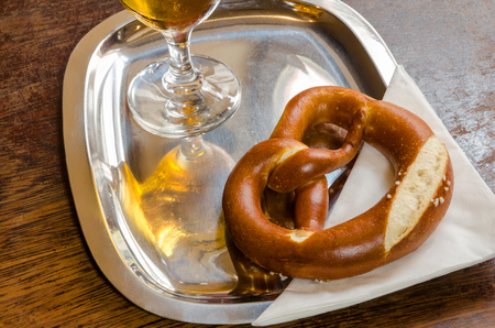 pretzel on a shiny metal tray with the reflection of the beer glass photo