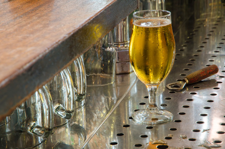 single beer: single beer glass in the working area behind the bar counter Stock Photo