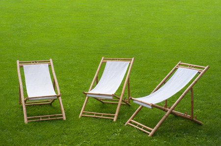 three folding chairs in a green park photo
