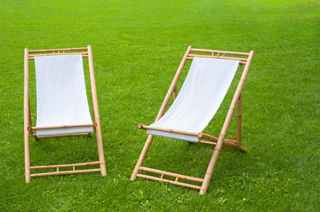 two folding chairs in a green park photo