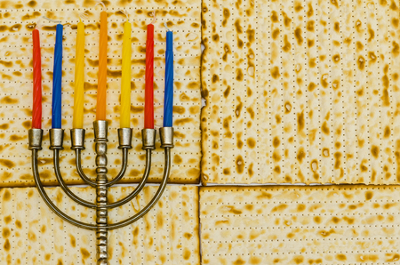 Menorah with colorful candles in front of Matzot photo