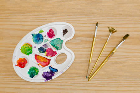 smudges: palette with smudges of paint and brushes on a wooden table