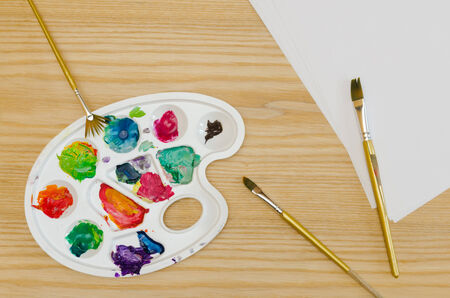 smudges: palette with smudges of paint, brushes and paper sheets on a wooden table Stock Photo