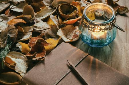 ノートブックとドライ フルーツの皮を持つテーブルでビンテージ キャンドル ランタン