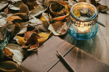 notebook and a vintage candle lantern on a table with dried fruit peel