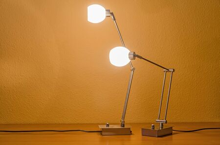 table lamps: two lit modern table lamps interacting with each other Stock Photo