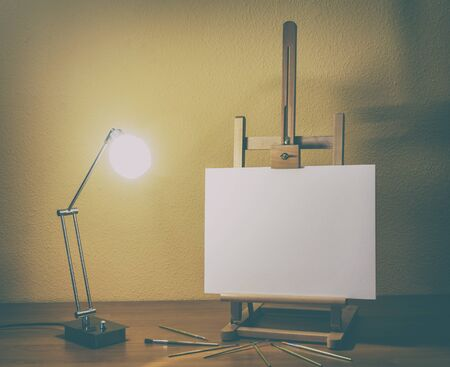 easel with canvas and brushes with a lit lamp on wooden table photo