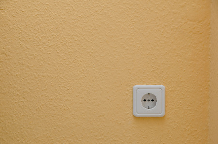 earthing: electric socket in a textured wall Stock Photo