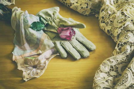 poetic: poetic composition with a rose lying on an elegant glove between a veil and a table cloth