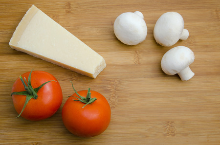 Parmesan cheese with tomatoes and mushrooms on wooden table photo