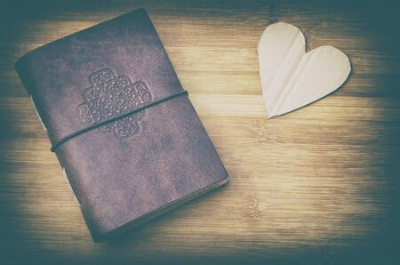 old notebook and a cardboard heart on a wooden table in vintage look photo