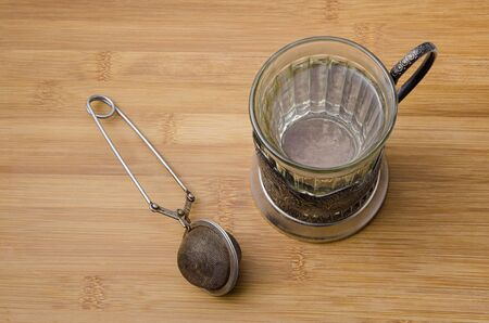 tea infuser: top view of retro tea cup with hot water and a mesh tea infuser on wooden table