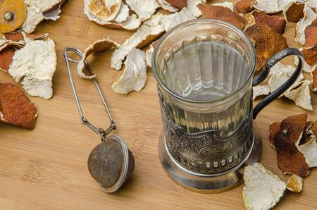 infuser: retro tea cup with hot water and a mesh tea infuser surrounded by dry citrus peel on wooden table Stock Photo