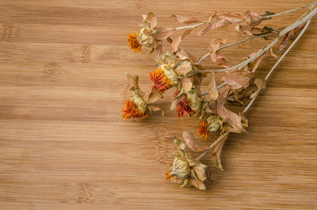withered: dry withered flowers on wooden surface
