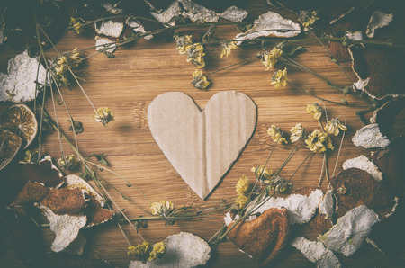 cardboard heart surrounded by a frame of dry citrus peel and withered flowers on a wooden table in vintage look photo