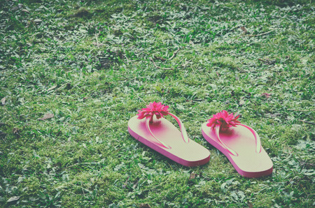 flipflops: two playful pink flip-flops on green grass. vintage filter effects.