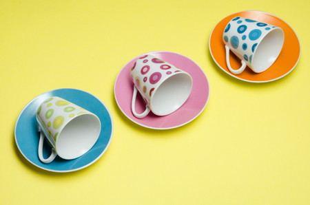 group of colorful espresso cups and plates on yellow background photo