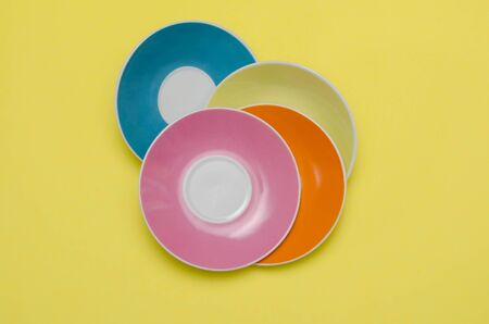 artful: artful arrangement of colorful plates on yellow background