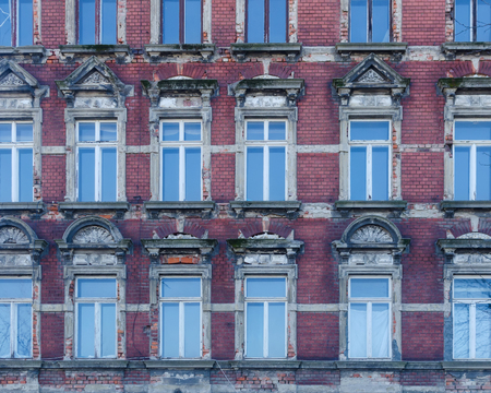 facade of an old abandoned building with windows reflecting the blue sky photo