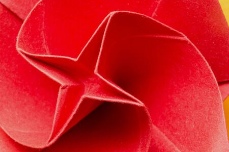 Abstract macro of a red stylized paper origami rose flower with plus shape in the middle. Top view. photo